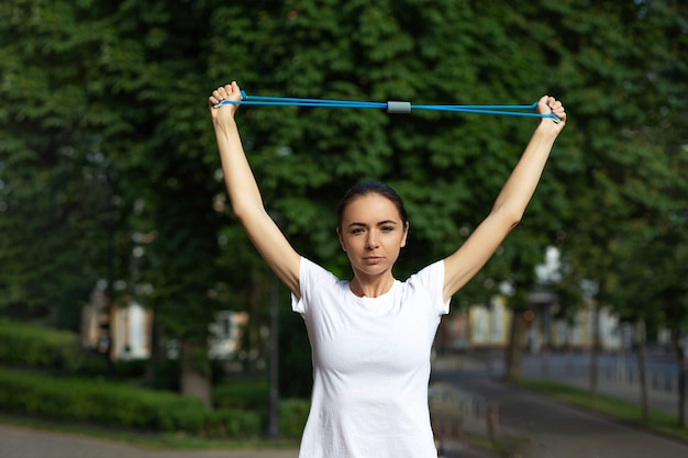 Attraente ragazza sportiva che si allena con le mani con banda di resistenza blu al parco