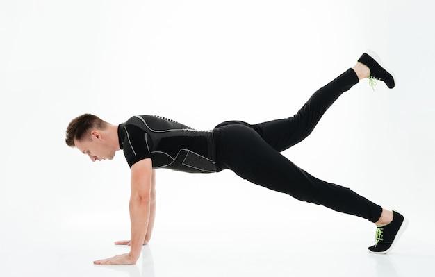 Lo sportivo forte e attraente fa esercizi sportivi