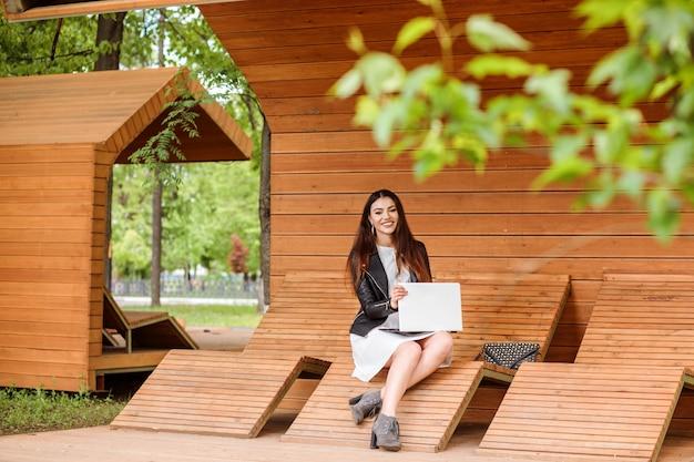 Attraente studentessa sta lavorando o studiando sul suo laptop all'aperto nel parco in estate o in primavera. la donna alla moda è vestita in giacca di pelle e abito bianco e si siede sulla moderna panca in legno