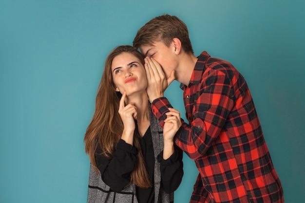 Coppie alla moda attraenti nell'amore divertendosi in studio sulla parete blu