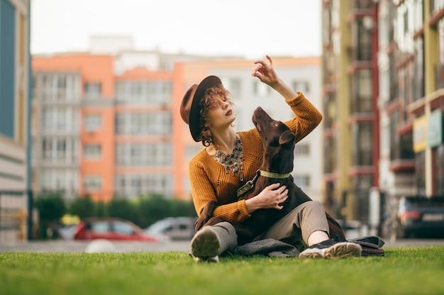Attraente ragazza alla moda hipster in cappello che gioca con il cane seduto sul prato