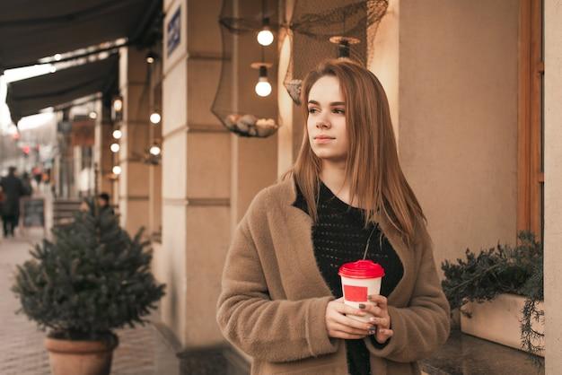 Attraente signora elegante indossa un cappotto beige caldo, si trova in strada con una tazza di caffè in mano e guarda di lato. ragazza in abiti primaverili sulla strada della città