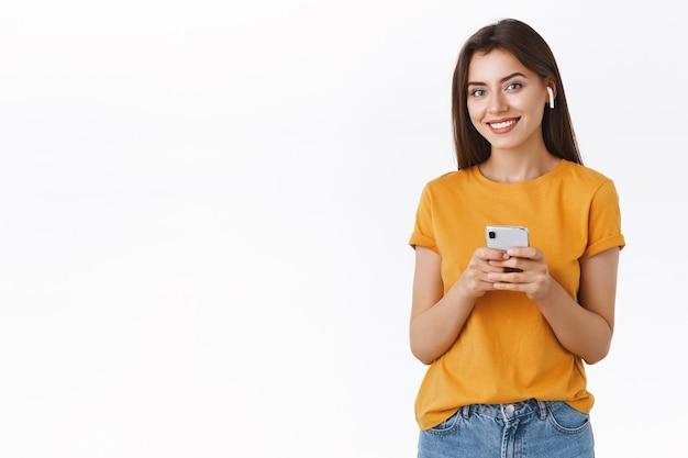 Attraente ed elegante donna tenera moderna in maglietta gialla indossa auricolari wireless, tiene in mano smartphone, macchina fotografica sorridente soddisfatta e felice mentre ascolta la canzone preferita durante il viaggio in aereo