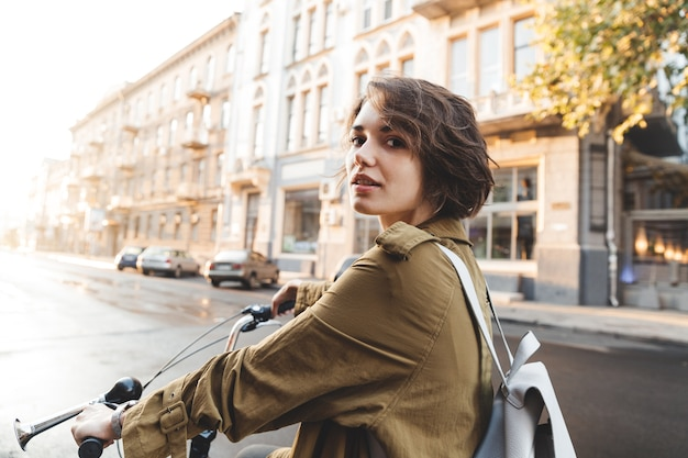 Attraente donna elegante che indossa cappotto in sella a una bicicletta su una strada cittadina