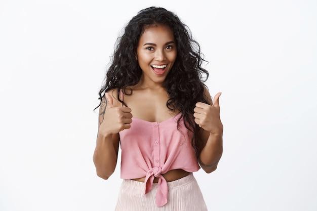 Attraente donna alla moda con i capelli ricci in top rosa, mostra pollice in su, annuisce con accettazione, d'accordo con un buon piano, come un'idea, in piedi muro bianco