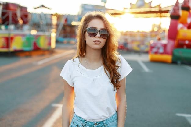 Attraente donna alla moda giovane hipster con capelli rossi in occhiali da sole in una maglietta bianca in jeans cammina in un parco di divertimenti in una calda giornata di sole primaverile