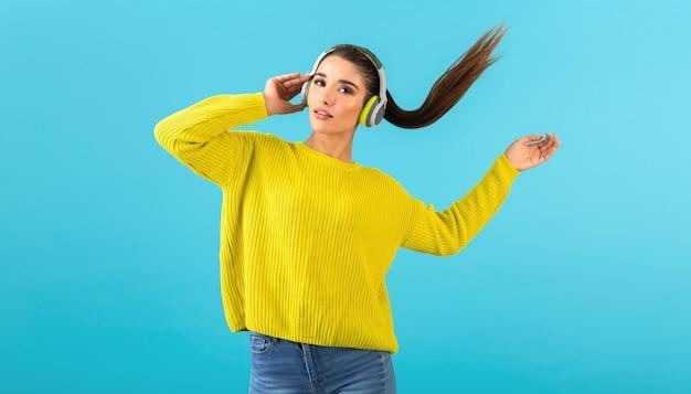 Attraente giovane donna elegante che ascolta la musica in cuffie senza fili felice indossa maglione giallo lavorato a maglia stile colorato moda in posa isolato su sfondo blu agitando la coda di capelli lunghi