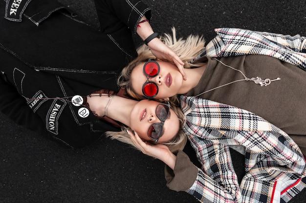 Attraenti giovani donne alla moda con occhiali alla moda in abiti alla moda giovanili che riposano sulla strada