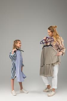Attraente donna alta che chiede consiglio alla sua sorellina mentre attacca un nuovo vestito al suo corpo