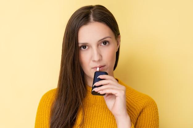 Attraente donna tartara con dispositivo elettronico di fumo sorridente e in posa isolato su sfondo giallo