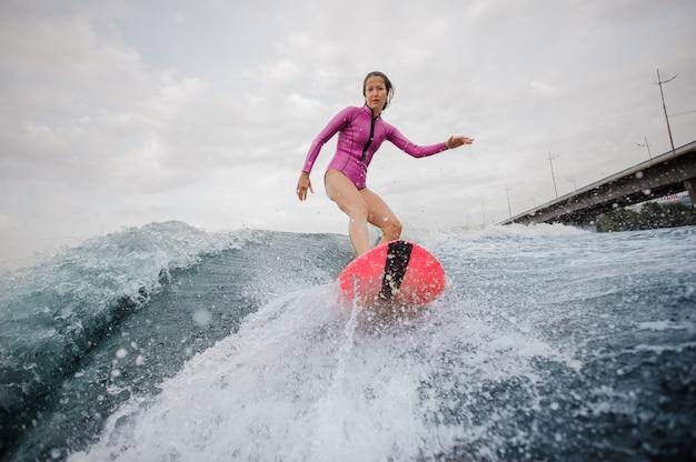 Ragazza attraente dell'adolescente in costume da bagno rosa che guida sul wakeboard arancio