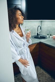 Attraente donna moderna premurosa che tiene un bicchiere di acqua di cetriolo in una mano