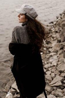 Attraente ragazza turistica viaggia in piedi vicino al lago