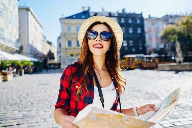 Attraente ragazza turistica con capelli castani che indossa cappello, occhiali da sole e camicia rossa, che tiene la mappa al vecchio sfondo della città europea e sorridente, in viaggio, ritratto.
