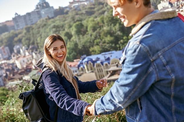 Un'attraente ragazza viaggiatrice sta trascinando il suo ragazzo per andare con lei