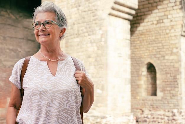 Donna senior del viaggiatore attraente che visita la cattedrale a barcellona. felice pensionato che si gode le vacanze e la storia