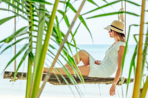 Attraente donna viaggiatore in vacanza estiva seduto a un'altalena su una spiaggia tropicale