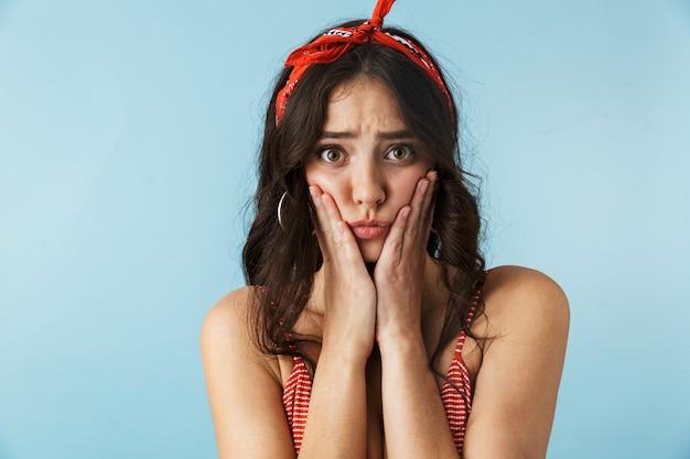 Attraente infelice giovane donna sconvolta che indossa abiti estivi in piedi isolato su blu