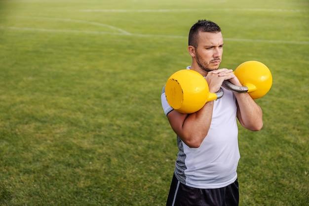 Giocatore di calcio con la barba lunga attraente in forma facendo resistenza con campane bollitore.