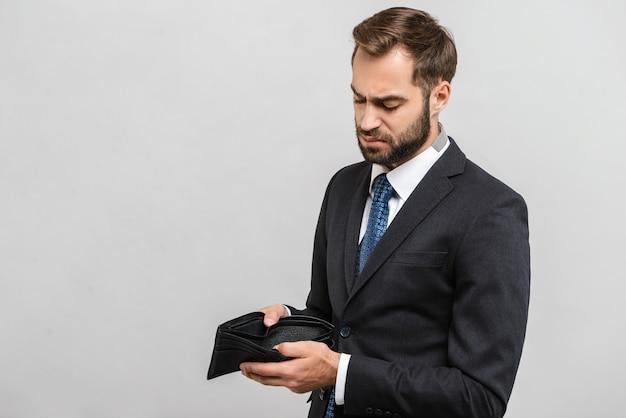 Attraente giovane uomo d'affari sconvolto che indossa un abito in piedi isolato su un muro grigio, mostrando banconote in denaro