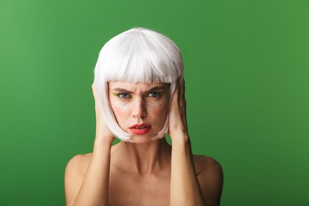 Attraente giovane donna in topless sconvolta che indossa i capelli bianchi corti in piedi isolato, copre le orecchie