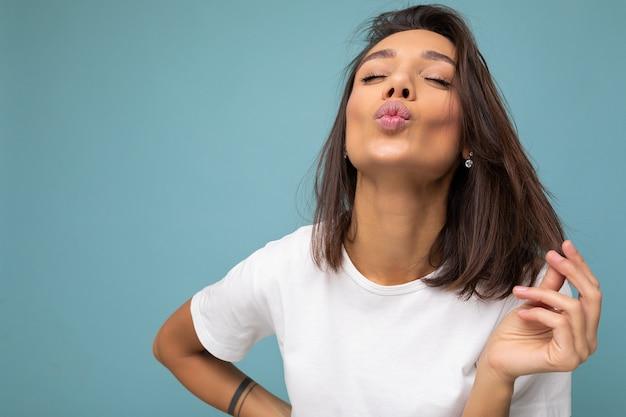 Attraente accattivante adorabile bella giovane donna bruna sexy in maglietta bianca casual per mockup isolato su sfondo blu con spazio libero e dando bacio