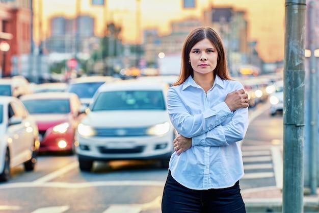 Attraente donna di 26 anni in camicia bianca è in piedi sulla strada vicino al traffico alla sera d'estate.