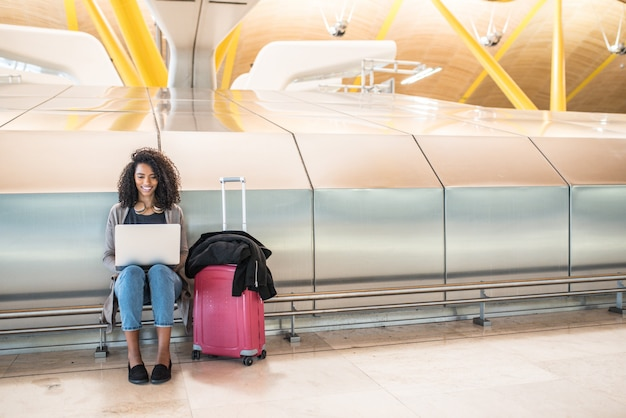 Donna attraente all'aeroporto che si siede e che lavora con il computer portatile