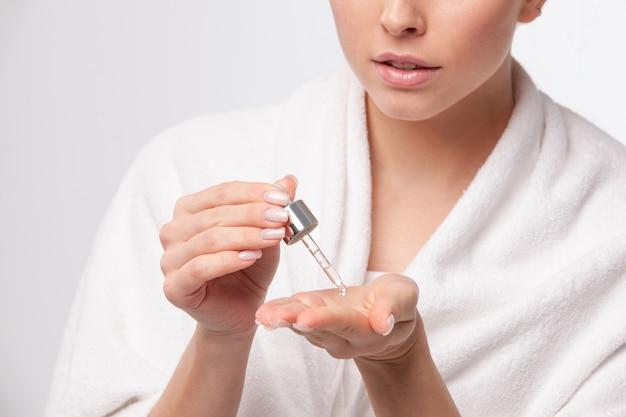 Donna attraente che applica il trattamento sulla sua mano