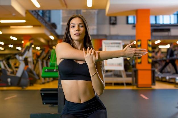 Atleta donna attraente in un top nero corto e pantaloni sportivi neri facendo un esercizio in palestra allungando le braccia