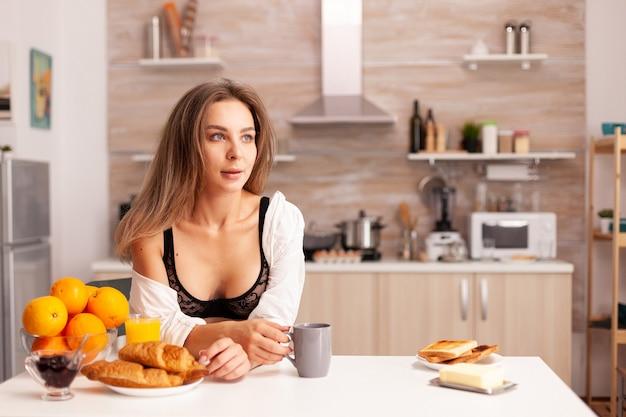 Donna attraente in ligerie nera che si rilassa con il caffè durante la colazione giovane signora sexy e seducente con tatuaggi che beve succo d'arancia fatto in casa sano e naturale, rinfrescante domenica mattina