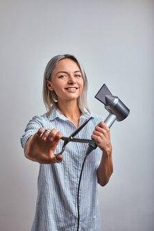 Parrucchiere biondo donna attraente con strumento professionale in posa sulla macchina fotografica, sfondo grigio. copia spazio, banner pubblicitario, concetto di bellezza.