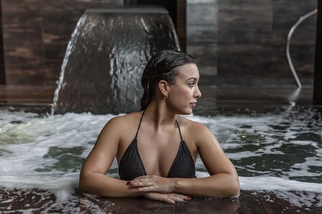 Donna attraente agghiacciante in piscina termale
