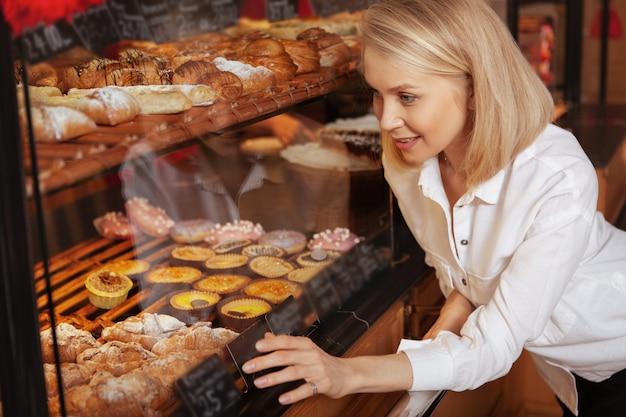 Donna attraente che sceglie deliziosi dessert dalla vetrina al negozio di panetteria