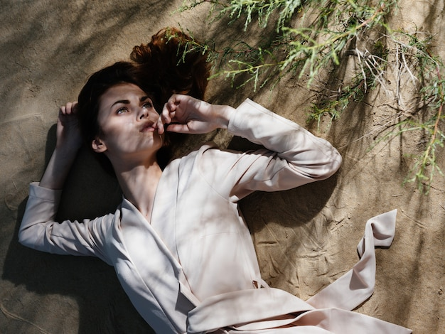 La donna attraente in cappotto si trova sullo stile di vita estivo di sabbia