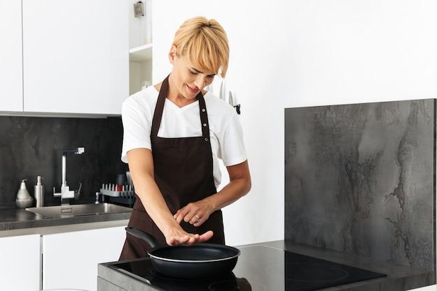 Donna attraente che cucina con una padella su una stufa mentre si trovava in cucina a casa