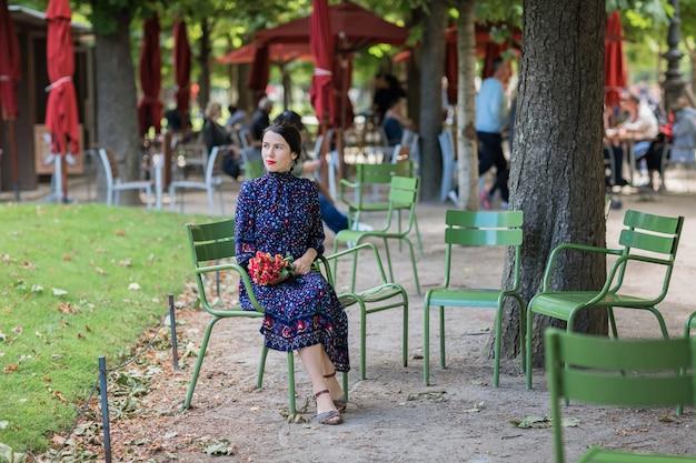 Donna attraente in un vestito blu scuro che si siede su una sedia nel parco