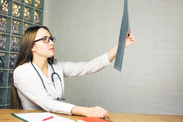 Medico donna attraente guardando i risultati dei raggi x