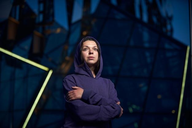 La donna attraente si è vestita in una maglia con cappuccio del centro nella città