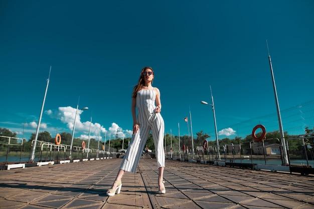 Donna attraente vestita con abiti eleganti che si gode un bel tempo soleggiato mentre si cammina