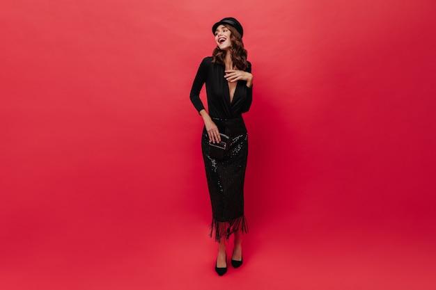 Attraente donna in elegante abito nero e berretto ride sul muro rosso