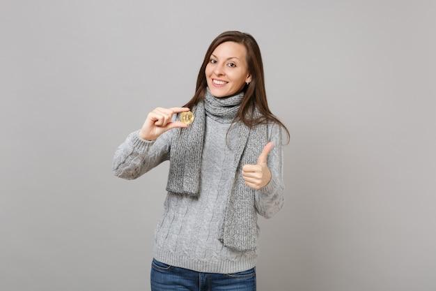 Donna attraente in maglione grigio, sciarpa che mostra pollice in su tenere bitcoin, valuta futura isolata su sfondo grigio. stile di vita sano, emozioni delle persone, concetto di stagione fredda. mock up copia spazio.