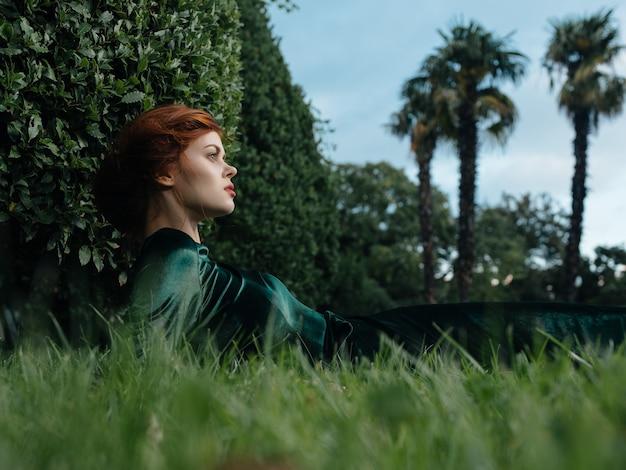 La donna attraente in un vestito verde si trova sulla vista favolosa del giardino dei cespugli di erba