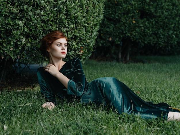 La donna attraente in vestito verde si trova sulla decorazione di fantasia di fascino del prato
