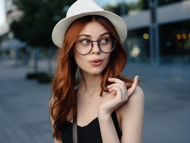 Donna attraente in un cappello all'aperto emozioni estive