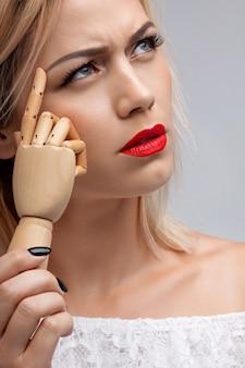 Donna attraente che tiene una mano di legno