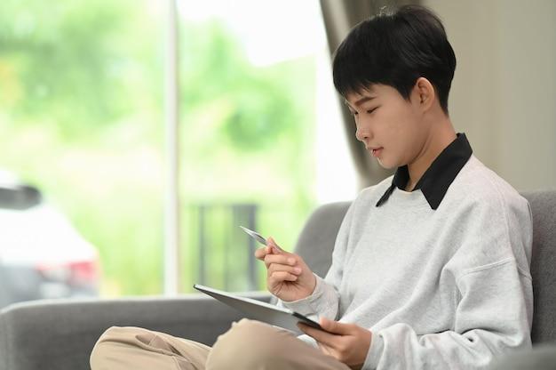 Una donna attraente sta tenendo la carta di credito e sta utilizzando il tablet a casa