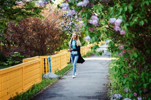 La donna attraente sta camminando attraverso il vicolo lilla in primavera. la studentessa sta trascorrendo del tempo in campagna.