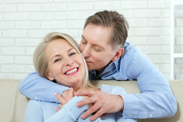 Uomo e donna attraente, la abbraccia da dietro e la bacia sul divano
