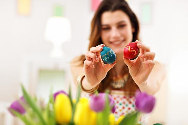 Donna attraente che dipinge le uova di pasqua a casa